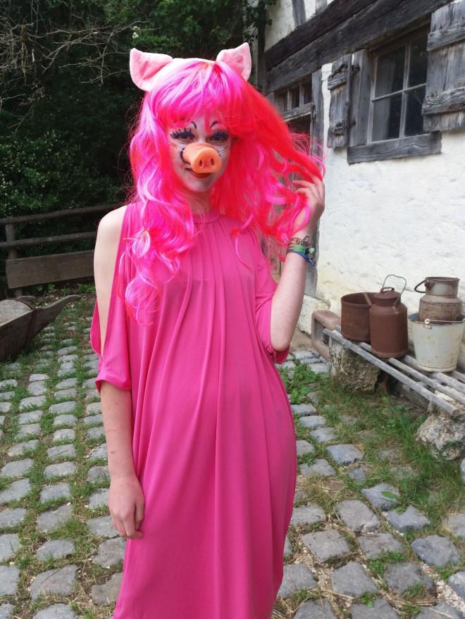 Schülerin im pinken Schwein-Kostüm
