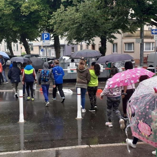 Kinder mit Regenschirmen überqueren zu Fuß eine Straße