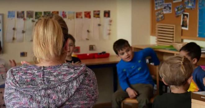 Kinder sitzen vor einer Erzieherin im Kindergarten