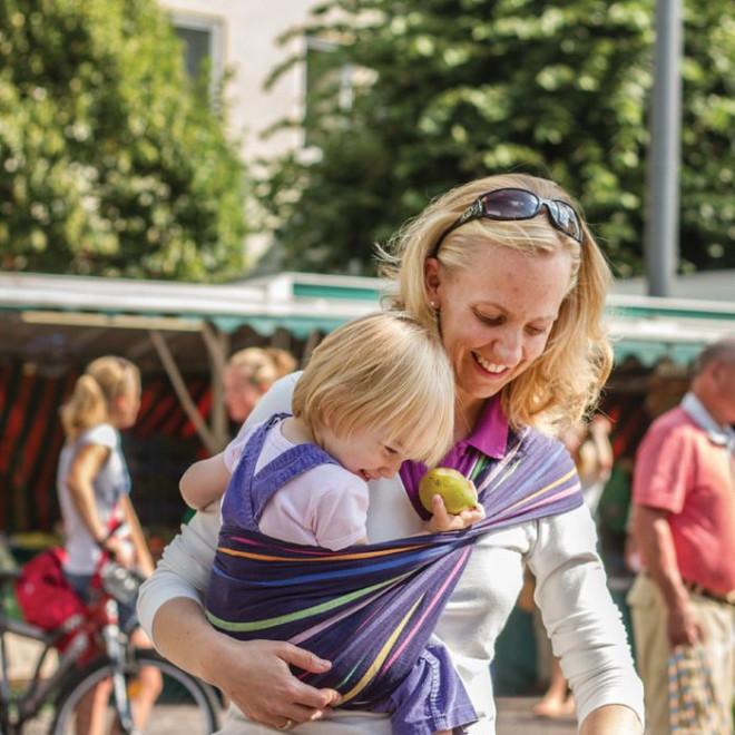 Eine Mutter mit ihrem Kind im Tragetuch beim Einkaufen auf dem Markt