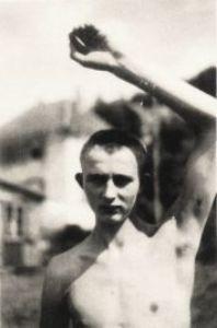 Schwarz-Weiß-Aufnahme eines Häftlings mit freiem Oberkörper, der den linken Arm hebt.