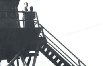 Schwarz-Weiß-Aufnahme von zwei Männern auf einem hölzernen Wachturm.
