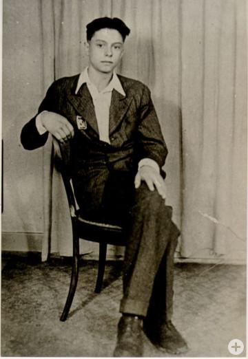 Schwarz-Weiß-Aufnahme eines Jugendlichen auf einem Stuhl.
