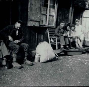 Schwarz-Weiß-Aufnahme von displaced persons vor einer Baracke.